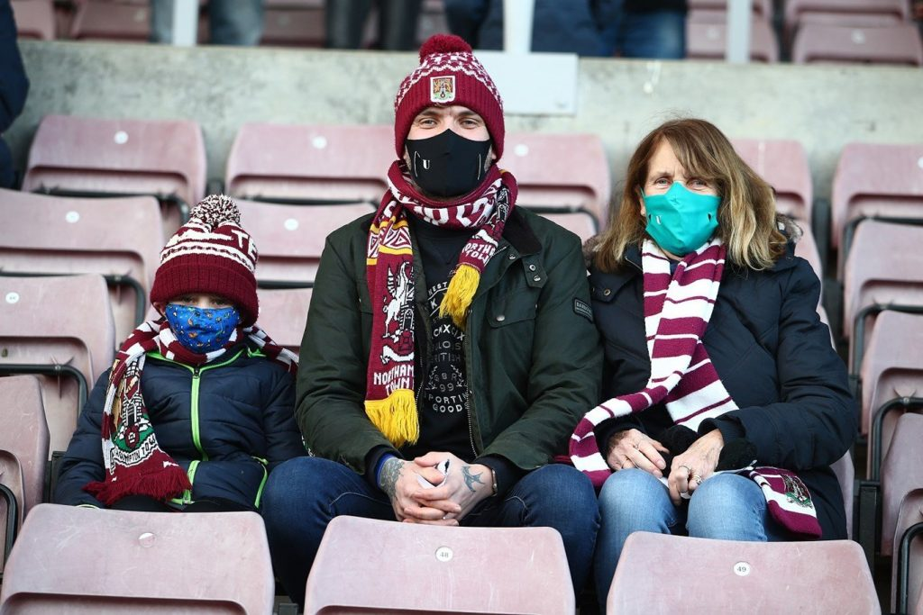 3 people sit in their seats at Sixfields